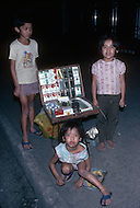 Child street vendors in Bangkok, Thailand selling trinkets - Child labor as seen around the world between 1979 and 1980 - Photographer Jean Pierre Laffont, touched by the suffering of child workers, chronicled their plight in 12 countries over the course of one year.  Laffont was awarded The World Press Award and Madeline Ross Award among many others for his work.