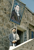Hazara Spiritual and political Leader Mohammad Karim Khalili under the portrait of former Leader Ustad Abdul Ali Mazari in Yakawlang. The day he was elect by the Hazara Shoura in Mazar e Sharif, He flight by helicopter to Yakawlang and become the successor of Mazari. ..Abdul Karim Khalili is son of Mohammad Aslam. Karim Khalili was born in 1329 H.S. (1950) in Qol-e-Khesh Behsud. It means, a part of Behsud district, province of Maidan. Today Abdul Karim Khalili is the current Leader of Hizb-e-Wahdat and Vice President of Afghanistan...Abdul Ali Mazari was born 1946 in the village of Charkint, south of the city of Mizar-i-Shrief, in northern Afghanistan, into a Hazara family. That is the reason he used surname Mazari..He studied theology in Qom, Iran. There he got involved in the Mujahideen resistance movement against the Russians in Afghanistan. He was one of the leading figures in unifying the Hazara resistance parties into one unified party, Hizb-i-wahdat (Unity Party). This party played a leading and positive role in voicing and fighting for the oppressed Hazara people of Afghanistan. During the civil war it held all the Hazara-populated areas in Afghanistan. He was highly respected figure among the Hazaras, for he had given them a voice and pride, he was affectionately called Baba (father) Mazari and Ustad (teacher) Mazari..During the siege of Kabul, the Talibans lured him for negotiations and then brutally killed him on Sunday 21/12/1373 (March 11 1995). His funeral procession march on foot from Kabul to Bamiyan and then Mazar-i-Sharif, where he was buried.
