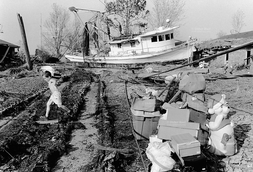 USA. Louisiana. New Orleans. St Bernard Parish. Chalmette area. Aftermath of hurricane Katrina. A fishing boat lies in a street near empty houses. The houses were flooded and the ground is covered by oil spillt over from the Murphy Oil Refinery plant. A family selects its unflooded belongings, like cardboard boxes and Winnie the pooh, dressed as Santa Claus - the father Christmas. A child plays in the road and jumps over dirty messy black oil. Oil disaster. Contaminated land. Industrial pollution and toxic waste.  © 2005 Didier Ruef