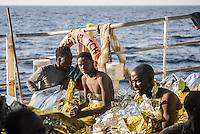 Die Sea Watch-2 Crew war am Freitag den 21. Oktober 2016 in den fruehen Morgenstunden waehrend ihrer 13. SAR-Mission vor der libyschen Kueste zu einer Position ausserhalb der 12 Meilenzone gerufen worden. Es war ein Fluechtlingsschlauchboot gesichtet worden. Als die Sea Watch-2 dort eintraf sah sie ca. 150 Menschen zusammengepfercht in einem ueberfuellten Schlauchboot sitzen. Eine Versorgung der Menschen auf dem Fluechtlingsschlauchboot mit Rettungswesten durch die Rettungs Boote der Sea Watch-2 wurde von der libyschen Kuestenwache unterbunden. Ein Soldat der Kuestenwache enterte das Schlauchboot vom Bug und machte sich dann an dem Aussenbordmotor zu schaffen. Auf dem Weg dahin schlug und trat er die Gefluechteten ein. Nach einigen Minuten entfernte sich das Boot der Kuestenwache. Dann verlor der Bug des Schlauchbootes seine Luft und es brach Panik bei den Gefluechteten aus. Sie sprangen in das Wasser und versuchten zum Schiff Sea Watch-2 zu gelangen. Die Crew warf ihnen Schwimmwesten und Rettungsringe zu, die Besatzungen der Rettungsboote der Sea Watch-2 zogen Menschen aus dem Meer, dennoch sind bis zu 30 Menschen ertrunken. Vier Ertrunkene konnten von der Sea Watch geborgen werden.<br /> Im Bild: Gerette Gefluechtete an Bord der Sea Watch-2.<br /> 21.10.2016, Mediterranean Sea<br /> Copyright: Christian-Ditsch.de<br /> [Inhaltsveraendernde Manipulation des Fotos nur nach ausdruecklicher Genehmigung des Fotografen. Vereinbarungen ueber Abtretung von Persoenlichkeitsrechten/Model Release der abgebildeten Person/Personen liegen nicht vor. NO MODEL RELEASE! Nur fuer Redaktionelle Zwecke. Don't publish without copyright Christian-Ditsch.de, Veroeffentlichung nur mit Fotografennennung, sowie gegen Honorar, MwSt. und Beleg. Konto: I N G - D i B a, IBAN DE58500105175400192269, BIC INGDDEFFXXX, Kontakt: post@christian-ditsch.de<br /> Bei der Bearbeitung der Dateiinformationen darf die Urheberkennzeichnung in den EXIF- und  IPTC-Daten nicht entfernt werden, diese sind in di
