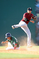 Shortstop Yeixon Ruiz (5) of the Savannah Sand Gnats turns a double play as Carlos Asuaje (20) of the Greenville Drive tries to take him out in a game on Sunday, June 22, 2014, at Fluor Field at the West End in Greenville, South Carolina. Greenville won, 7-3. (Tom Priddy/Four Seam Images)