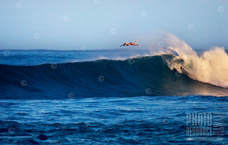 Young woman surfer wipes out on a large winter wave at Sunset Beach on North Shore of Oahu.