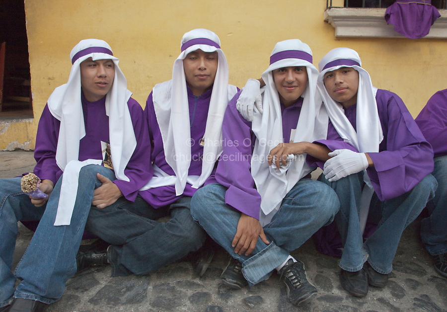 Antigua, Guatemala.  Young Men Relaxing after Finishing their Turns as Cucuruchos, Carrying a Float (Anda) in a Religious Procession during Holy Week, La Semana Santa.