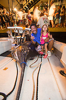 Bomboy Lanes, captain of the fishing boat Lana Kila, with a little girl and a Pacific blue marlin grander (1,000-lb. or more fish) on deck, Kailua-Kona, Big Island.