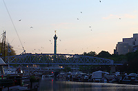 Paris Right Bank: A view of the port de l'Arsenal in Paris (it links the Canal de Saint Martin to place de la Bastille), with its boats, its typical bridge, and the column of July on the background, in the sunrise light. There are many seagulls and the water surface is flat.<br /> <br /> You can download this file for (E&PU) only, but you can find in the collection the same one available instead for (Adv).
