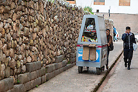 Peru, Cusco.  Woman Pushing her Vendor's Cart Down a Street.