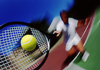 700-00032778                                Blurred view of Man Playing Tennis / Ball and racket sharp