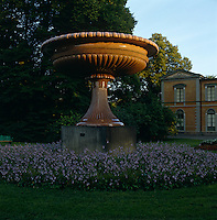 An enormous granitell vase, made in 1825 at the Alvdalen porphyry works stands encircled by a bed of flowers before the summer palace of Rosendal