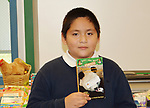 Braeburn ES student Adolfo likes pandas, so he was happy to find a book about pandas and other endangered species