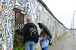 Tourists visit the Eastside Galleryin the rain.  118 artists from around the world painted murals on the longest remaining piece of the Berlin wall in 1990.  Berlin, Germany