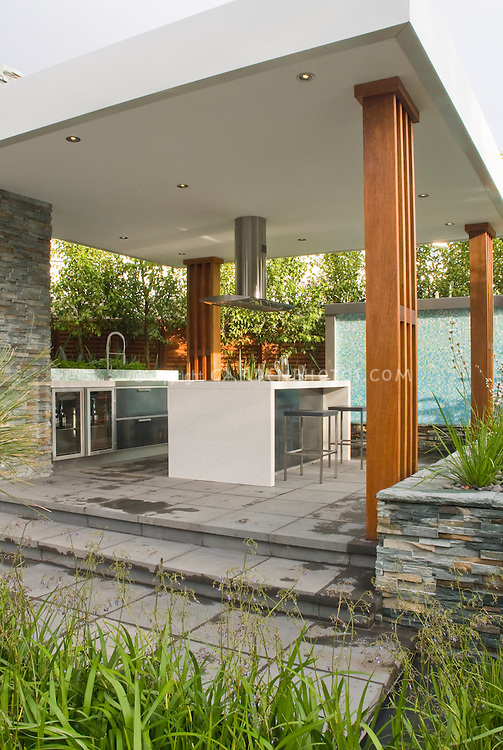 Outdoor Kitchen & Covered Patio home landscaping with dining table, waterfall water feature, ornamental grasses plants, hood, modern design, stairs steps, deck, sink, oven, classy and sophisticated room outside