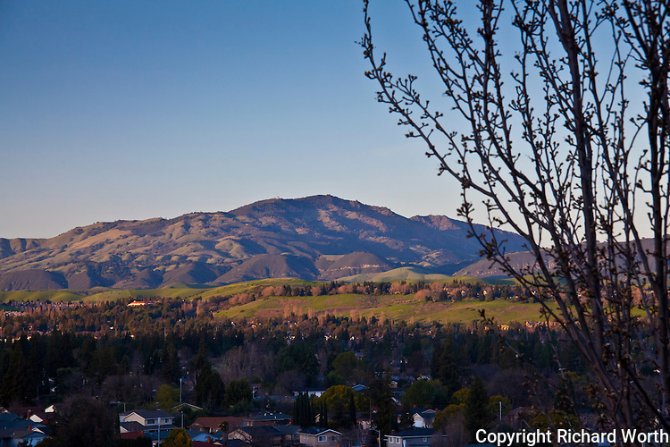 Mount Diablo still in direct but tinted light, as  the setting sun casts a long, creeping shadow across the San Ramon Valley.