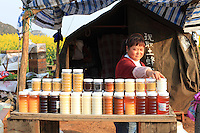 Luoping, Yunnan. A beekeeper presents her honey made from diverse flowers.