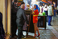 Pictured: A woman in a Lifeguard dress speaks to door staff. Sunday 31 December 2017 and 01 January 2018<br /> Re: New Year revellers in Wind Street, Swansea, Wales, UK