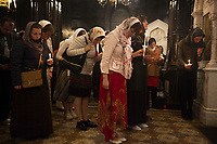 Switzerland. Geneva. Easter at the Russian Church. The church is a lovely 19th-century Russian Orthodox church and designed in a Byzantine Moscovite style. The church's full name is Cathédrale de l'Exaltation de la Sainte Croix. A group of believers, all women with a scarf on their heads, hold candles in hands on the night of Easter Sunday. The nighttime liturgy is a blessing of Easter fire with candles and the celebration of the Easter Proclamation of the Resurrection of Jesus Christ. Easter, also called Pascha or Resurrection Sunday is a festival and holiday celebrating the resurrection of Jesus from the dead, described in the New Testament as having occurred on the third day of his burial after his crucifixion.The Russian church serves not only the Russian community but also Bulgarians, Serbs, Coptic Christians and other Orthodox worshippers who do not have their own church in Geneva. 16.04.17 © 2017 Didier Ruef