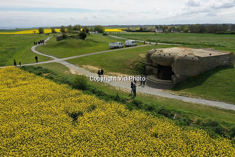 Foto: VidiPhoto<br /> <br /> LONGUES SUR MER – De Franse koolzaadvelden staan op dit moment in volle bloei en vormen een felgele 'ontploffing' rond de verdedigingswerken van de voormalige Duitse Atlantikwall in Normandië. Omdat veel bezoekers de drukke 75-jarige herdenking van de invasie in juni willen mijden, zijn er nu meer toeristen dan  gebruikelijk in mei. Met 1,4 miljoen ha. koolzaad is Frankrijk nog steeds de grootste producent van Europa. Door de droge omstandigheden tijdens het inzaaien vorig jaar herfst wordt daar echter 15-20 procent minder opbrengst verwacht. Uit het zaad wordt koolzaadolie getrokken, onder meer gebruikt voor biodiesel. Per hectare kan ongeveer 1300 liter biodiesel geproduceerd worden. De koolzaadvezels zijn vitaminerijk en worden gebruikt als krachtvoer voor het vee.