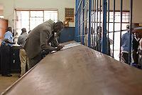 Detective Simiyu signing  aprisoner out of  the holding cells to conduct an interrogation.