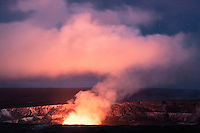 A colorful glowing plume of smoke rises out of Halema'uma'u Crater at night in Hawai'i Volcanoes National Park, Big Island.