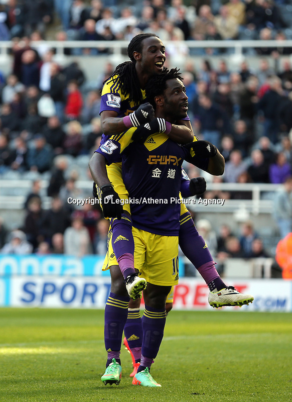 Pictured: Wilfried Bony of Swansea celebrating his goal from the penalty spot after Marvin Emnes -who has climbed on him- was brought down in the box in stoppage time. Saturday 19 April 2014<br /> Re: Barclay's Premier League, Newcastle United v Swansea City FC at St James Park, Newcastle, UK.