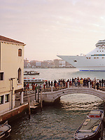 Tourists crowd a bridge over a canal as the Royal Caribbean cruise ship Splendour of the Seas looms large in the background. Over 600 cruise ships moor in the city of Venice every year, bringing in a near-continuous supply of visitors.