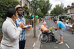 Disabled older man in community being helped. Street Party. The Big Lunch. Brunswick Street Walthamstow Village London E17 England 2009.
