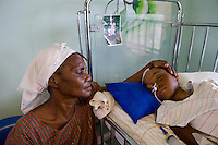 Effects of the January 12, 2010 earthquake. St. Damiem Hospital. Grandmother with Mohanine Johanne Baptiste. The little girl is brain damaged and won't make it but the doctors haven't told the mother yet. There's a photo behind her when she was a happy healthy little girl.
