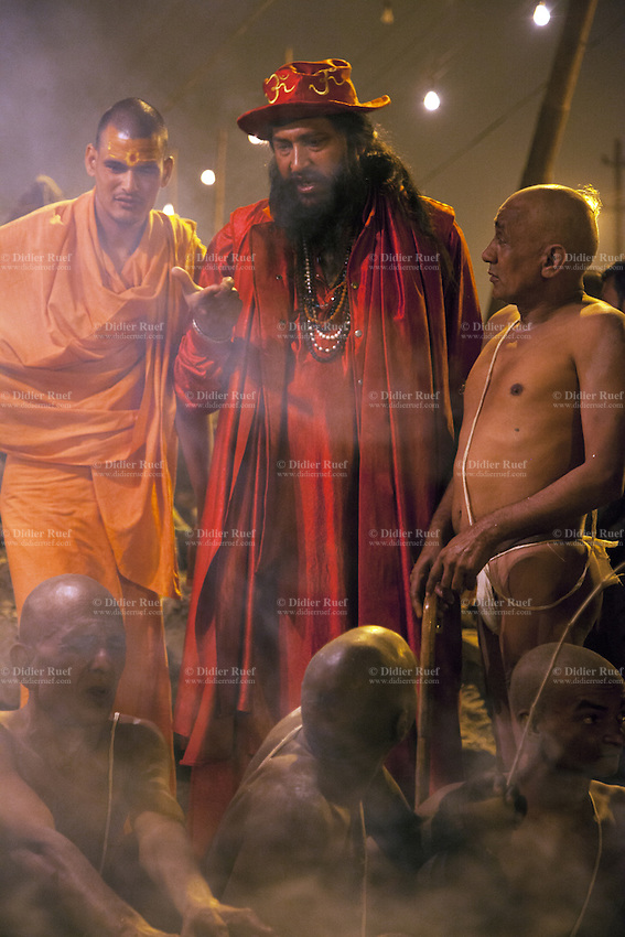 """India. Uttar Pradesh state. Allahabad. Maha Kumbh Mela. Hindu holy men of the Juna Akhara sect participate in rituals that are believed to rid them of all ties in this life and dedicate themselves to serving God as """"Naga"""" or naked holy men. A group of Naga Sadhus with a seer dressed with red clothes and a hat at night in Sangam. The Kumbh Mela, believed to be the largest religious gathering is held every 12 years on the banks of the 'Sangam'- the confluence of the holy rivers Ganga, Yamuna and the mythical Saraswati. The belief is that bathing and taking a holy dip will wash and free one from all the past sins, get salvation and paves the way for Moksha (meaning liberation from the cycle of Life, Death and Rebirth). In Hinduism, Sadhu (good; good man, holy man) denotes an ascetic, wandering monk. Sadhus are sanyasi, or renunciates, who have left behind all material attachments. They are renouncers who have chosen to live a life apart from or on the edges of society in order to focus on their own spiritual practice. The significance of nakedness is that they will not have any worldly ties to material belongings, even something as simple as clothes. This ritual that transforms selected holy men to Naga can only be done at the Kumbh festival. A Sadhu is usually referred to as Baba by common people. The Maha (great) Kumbh Mela, which comes after 12 Purna Kumbh Mela, or 144 years, is always held at Allahabad. Uttar Pradesh (abbreviated U.P.) is a state located in northern India. 6.02.13 © 2013 Didier Ruef"""