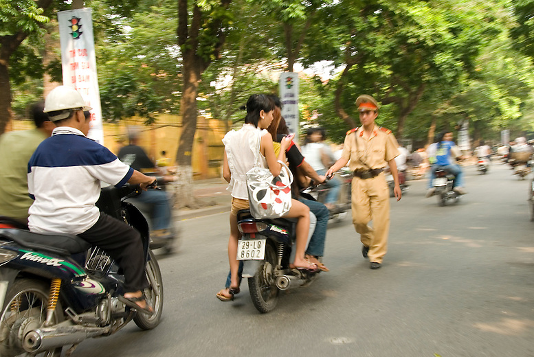 Where bicycles are the more traditional form of transportation, motorbikes are now the most popular form of transportation in Vietnam. With increased use of motorbikes, the Vietnamese are realizing they'll need to in force stricter road rules. A police officer or 'long faced man' as they're called by the locals walks down the road targeting multiple motorbike riders in Hanoi, Vietnam.