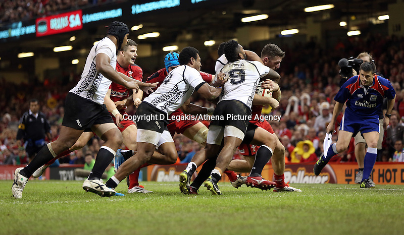 Pictured: Alex Cuthbert of Wales (R) is brought down by Waisea Nayacalevu (C) and Nikola Matawalu (9) of Fiji. Saturday 15 November 2014<br /> Re: Dove Men Series rugby, Wales v Fiji at the Millennium Stadium, Cardiff, south Wales, UK.