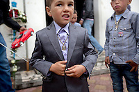 A child attends a baptism party. Buzescu is known for it's ultra-wealthy Roma and their bizarre mansions that line the main street. The Roma of Buzescu are part of the Kalderash clan and are known for being coppersmiths and dealing with metal scraps. After the fall of the communist regime in the late 80's, they stripped old factories of their metals and some made a small fortune re-selling them. They are also known for making cazane, copper stills that produce alcohol such as palinka, a plum brandy.