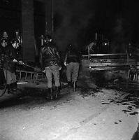 Nuit du 11 au 12 juin 1968. Scène de barricade : au 1er plan pompiers (vue de dos et de profil) en train d'éteindre le feu ; en arrière-plan barricade. Vue de nuit. Cliché pris durant les évènements de Mai 68 à Toulouse.