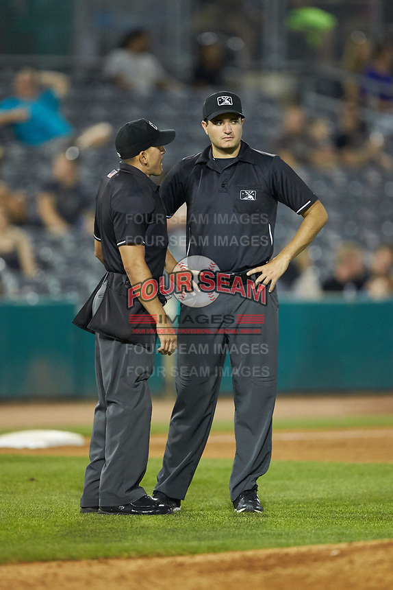 Home plate umpire Kelvis Velez (left) discusses a call with base umpire Ben Fernandez during the South Atlantic League game between the Lexington Legends and the West Virginia Power at Appalachian Power Park on June 7, 2018 in Charleston, West Virginia. The Power defeated the Legends 5-1. (Brian Westerholt/Four Seam Images)