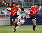 Argentine Lionel Messi (C) is tackled by Spain's Markel (L) and Zapater (R) in the quarter-finals of the FIFA World Youth Championship match at the Enschede Stadium in Enschede, the Netherlands June 25, 2005. Argentinian goalie Oscar Ustari and Juan Manuel Torres look on. REUTERS/Michael Kooren