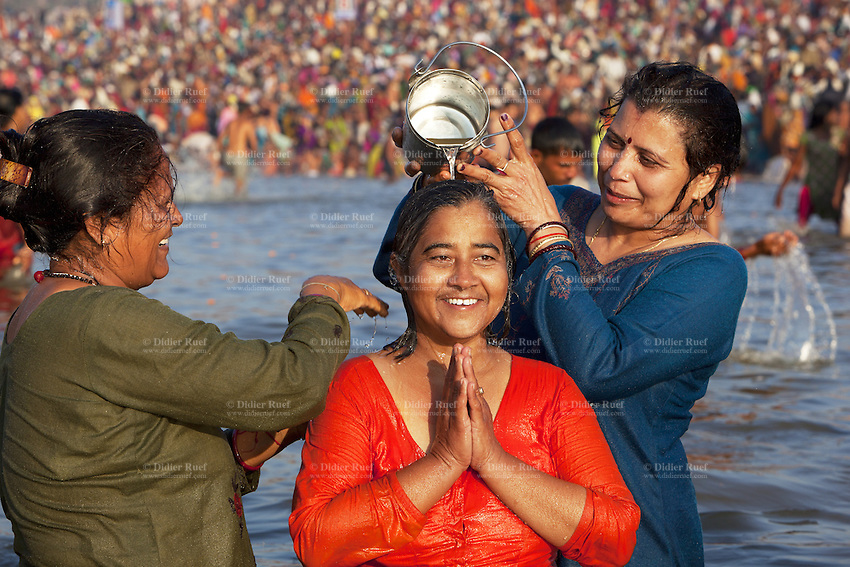 India. Uttar Pradesh state. Allahabad. Maha Kumbh Mela. Indian Hindu devotees take a holy dip at Sangam. Three women offer water to Mother Ganges because the river is considered a deity. One woman is praying. The Kumbh Mela, believed to be the largest religious gathering is held every 12 years on the banks of the 'Sangam'- the confluence of the holy rivers Ganga, Yamuna and the mythical Saraswati. In 2013, it is estimated that nearly 80 million devotees took a bath in the water of the holy river Ganges. The belief is that bathing and taking a holy dip will wash and free one from all the past sins, get salvation and paves the way for Moksha (meaning liberation from the cycle of Life, Death and Rebirth). Bathing in the holy waters of Ganga is believed to be most auspicious at the time of Kumbh Mela, because the water is charged with positive healing effects and enhanced with electromagnetic radiations of the Sun, Moon and Jupiter. The Maha (great) Kumbh Mela, which comes after 12 Purna Kumbh Mela, or 144 years, is always held at Allahabad. Uttar Pradesh (abbreviated U.P.) is a state located in northern India. 8.02.13 © 2013 Didier Ruef