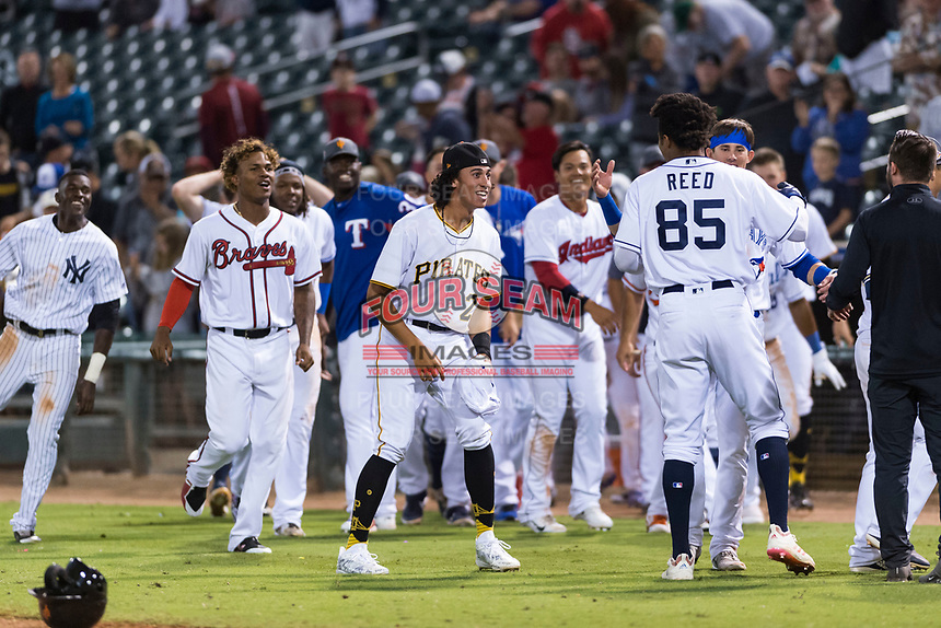 The AFL West left fielder Buddy Reed (85), of the Peoria Javelinas and San Diego Padres organization, prepares to get mobbed by his teammates including Cristian Pache (27), Cole Tucker (2), and Cavan Biggio (26) after scoring the winning run to win the Fall Stars game at Surprise Stadium on November 3, 2018 in Surprise, Arizona. The AFL West defeated the AFL East 7-6 . (Zachary Lucy/Four Seam Images)
