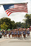 NEWTOWN, CT-1 September 2014-090114EC05--   The Newtown High School cheerleading squad crosses under a giant raised American flag during the Newtown Labor Day Parade Monday morning. Erin Covey Republican-American