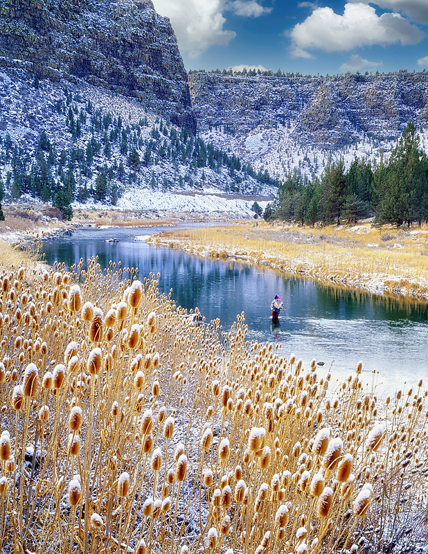 Fly fisherman on the Crooked River with snowfall. Oregon.