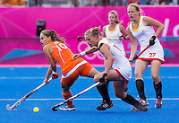 29 JUL 2012 - LONDON, GBR - Anne-Sophie van Regemortel (BEL) of Belgium (second from left) avoids a challenge from Kelly Jonker (NED) of Netherlands (left) during their women's London 2012 Olympic Games Preliminary round hockey match at the Riverbank Arena in the Olympic Park in Stratford, London, Great Britain .(PHOTO (C) 2012 NIGEL FARROW)