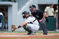 Charlotte Knights catcher Vinniy Rottino (4) sets a target as home plate umpire Paul Clemons looks on during the game against the Syracuse Chiefs at BB&T BallPark on June 1, 2016 in Charlotte, North Carolina.  The Knights defeated the Chiefs 5-3.  (Brian Westerholt/Four Seam Images)