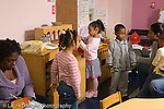 Preschool classroom ages 4-5 classroom visitor taking notes and observing horizontal children involved in pretend play female teacher interacting with children
