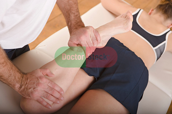 physiotherapist manipulates womans leg