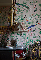Detail of a chinoiserie styled bedroom with fretwork chair, ceramics and hand painted wallpaper with exotic birds