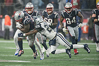 FOXBOROUGH, MA - NOVEMBER 24: Dallas Cowboys Safety Xavier Woods #25 brings down New England Patriots Runningback Sony Michel #26 during a game between Dallas Cowboys and New England Patriots at Gillettes on November 24, 2019 in Foxborough, Massachusetts.