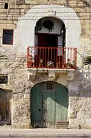 Marsaxlokk, Malta.  1806 Doorway, Balcony, Flowers facing the harbor.