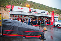 Jul 20, 2019; Morrison, CO, USA; NHRA fans take shelter under the awning of the Toyota Racing hauler in the pits as it rains during a delay to qualifying for the Mile High Nationals at Bandimere Speedway. Mandatory Credit: Mark J. Rebilas-USA TODAY Sports