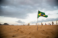Cariocas play soccer on the beach of Copacabana, a day to start the World Cup. In Brazil the sport is practiced on a daily basis and one can find it in every corner, on every surface. A flag of Brazil lies in the corner of the field. It is said that the Brazilian born with a ball attached to the foot. Rio de Janiero, Brazil.
