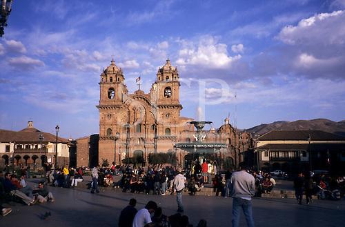 Cusco, Peru. La Compania Church in Plaza De Armas (Main Square) with people and fountain in forground.