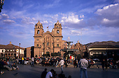 Cusco, Peru. La Compania Church in Plaza De Armas (Main Square) with people and fountain in forground.