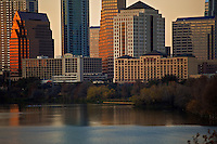The warm glow of the setting sun reflects on the iconic downtown Austin Cityscape as a Sculler Regatta team cuts across the water