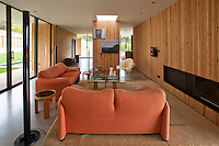 The interior features a long wood-clad wall and a waxed concrete floor and the living room is furnished with a pair of sofas by Vico Magistretti